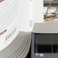 image of a book with its spine hanging off the side of the scanner so as to provide a better page scan.